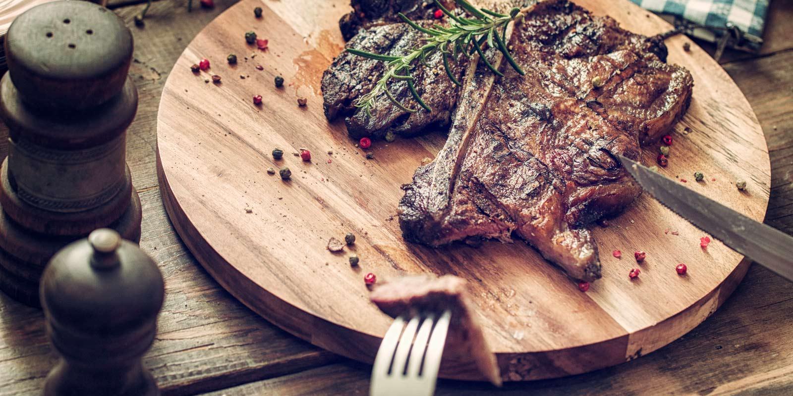 Gegrillltes Steakt liegt angeschnitten und saftig auf einem Holzteller