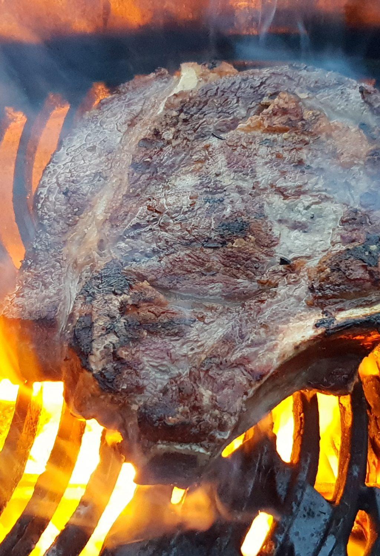 Steak auf dem Grill in einer Feuerflamme